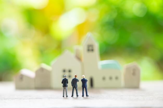 Uomini d'affari in miniatura di 3 persone in piedi con la schiena negoziare nel mondo degli affari.