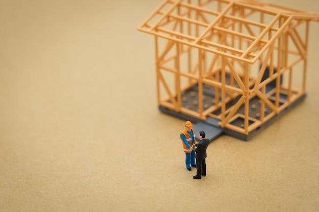 Uomini d'affari in miniatura in piedi analisi degli investimenti alloggio o investimento
