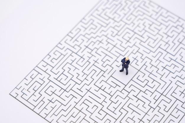 Uomini d'affari in miniatura in piedi nel centro del labirinto. idea imprenditoriale