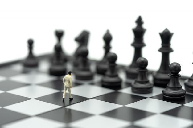 Uomini d'affari in miniatura in piedi su una scacchiera con un pezzo degli scacchi sul retro.