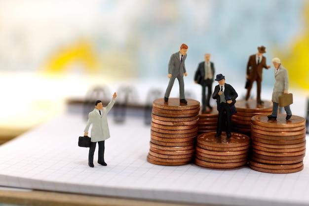 Uomini d'affari in miniatura in piedi sul gradino del denaro moneta