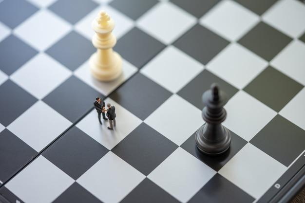 Uomini d'affari in miniatura persone in piedi su una scacchiera con un pezzo degli scacchi