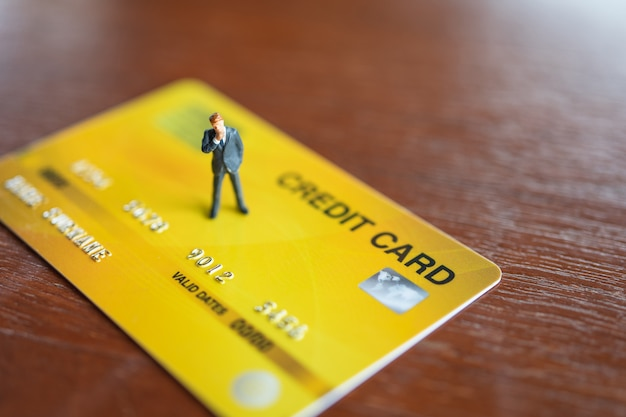 Uomini d'affari in miniatura persone in piedi sul modello di carte di credito