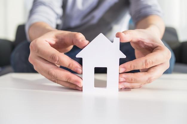Uomini d'affari in possesso di modello di casa in mano