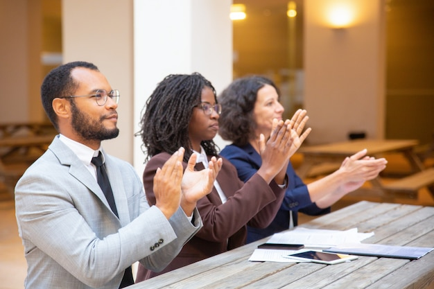 Uomini d'affari ispirati entusiasti che applaudono oratore