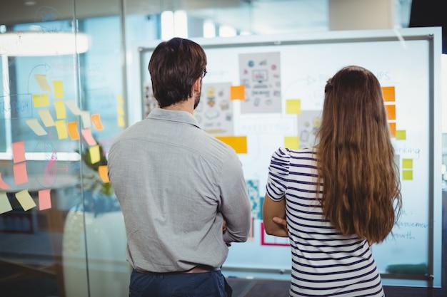 Uomini d'affari maschii e femminili che esaminano lavagna in ufficio
