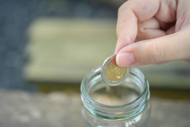 Uomini d'affari metti la moneta in un barattolo di vetro per risparmiare denaro, risparmiare denaro sugli investimenti,