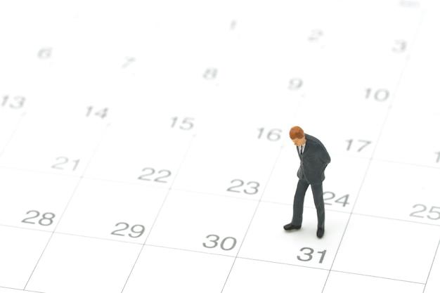 Uomini d'affari miniatura della gente che stanno sul calendario bianco