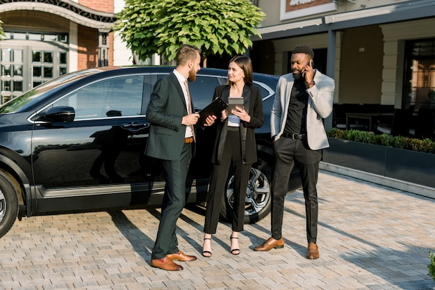 Uomini d'affari multirazziali, due uomini e una donna hanno un incontro di lavoro all'aperto, in piedi accanto a una macchina nera e edifici per uffici