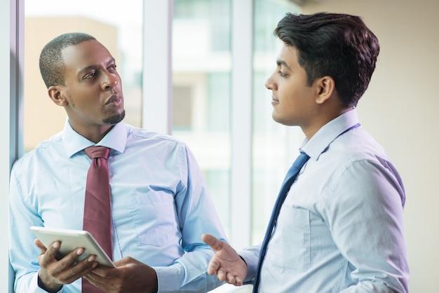 Uomini d'affari positivi che condividono piani e idee alla riunione