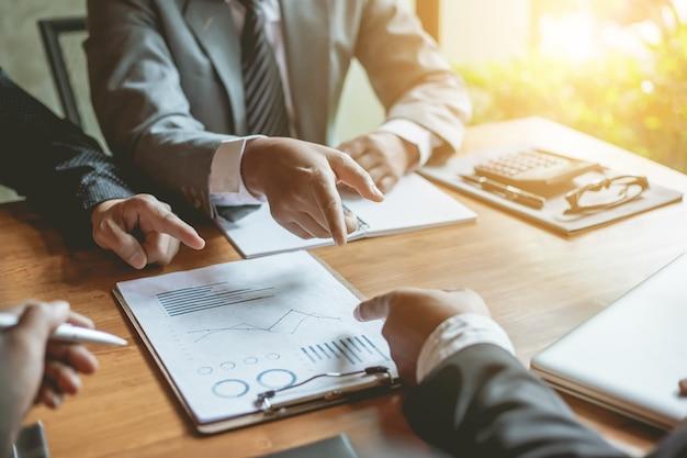 Uomini d'affari riuniti a lavorare con relazioni finanziarie