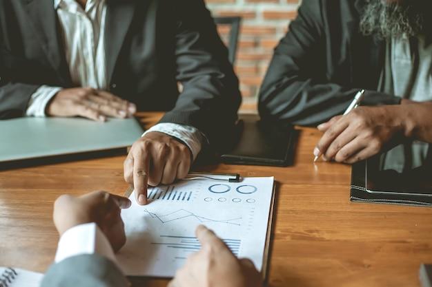 Uomini d'affari riuniti a lavorare con relazioni finanziarie.