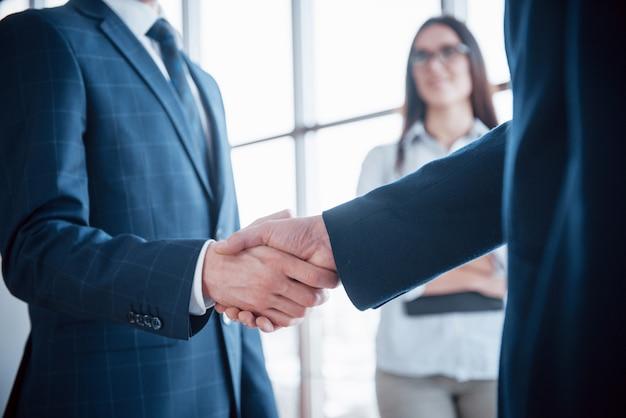 Uomini d'affari si stringono la mano, finendo un incontro