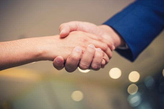 Uomini d'affari si stringono la mano, tra una riunione e l'altra in una sala per seminari