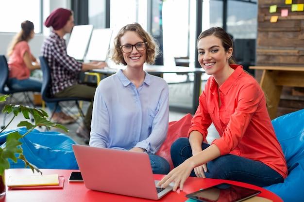 Uomini d'affari sorridenti che si siedono nell'ufficio con il computer portatile sulla tavola