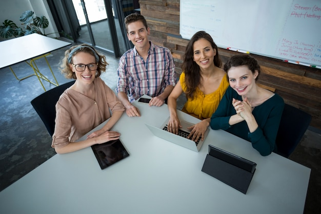 Uomini d'affari sorridenti che si siedono nell'ufficio con la compressa digitale e computer portatile sulla tavola