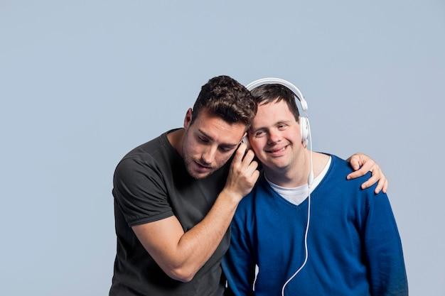 Uomini del colpo medio che ascoltano la musica tramite le cuffie