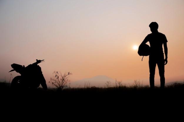 Uomini del motociclista con il tramonto.
