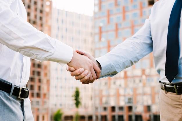 Uomini del primo piano in vestito che prendono un accordo