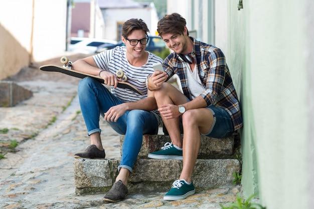 Uomini dell'anca che si siedono sui punti e che guardano allo smartphone nella città