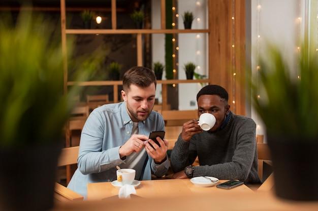 Uomini dell'angolo alto che bevono caffè