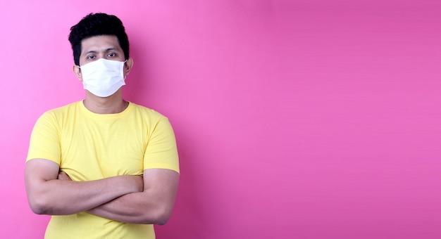 Uomini dell'asia che indossano una maschera isolata su fondo rosa in studio