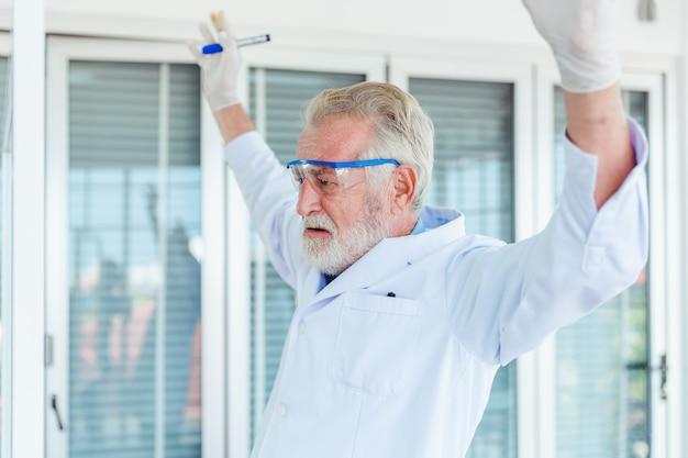 Uomini dell'insegnante di scienze che lavorano con le sostanze chimiche del bordo di vetro trasparente in laboratorio