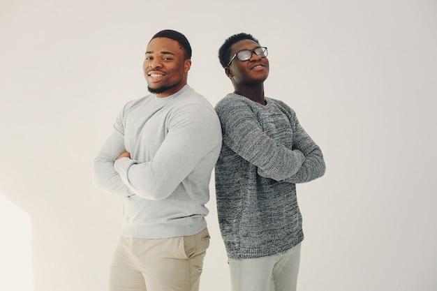Uomini di colore bei che stanno su una parete bianca