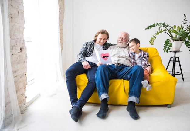 Uomini di diverse generazioni che leggono la carta regalo