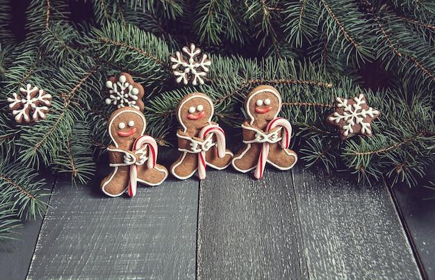 Uomini di pan di zenzero con i fiocchi di neve del bastoncino di zucchero che mettono su fondo di legno grigio.