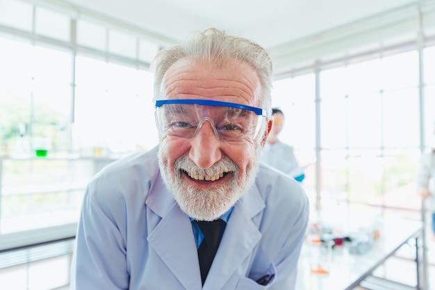 Uomini di scienza del ritratto che lavorano con i prodotti chimici in laboratorio