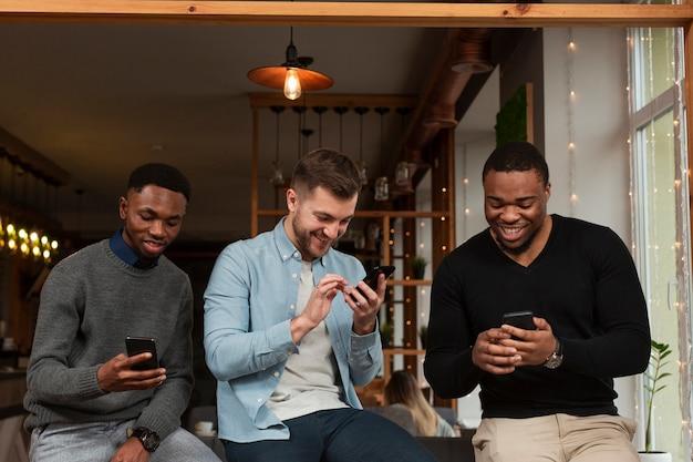 Uomini di smiley che controllano i telefoni