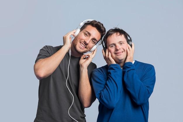 Uomini di vista frontale che ascoltano la musica tramite le cuffie