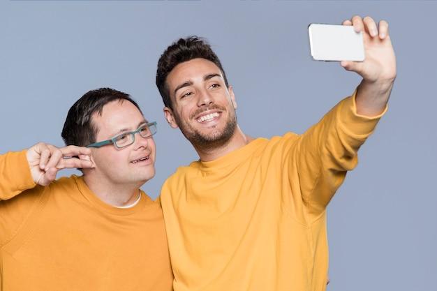 Uomini di vista frontale che prendono insieme un selfie