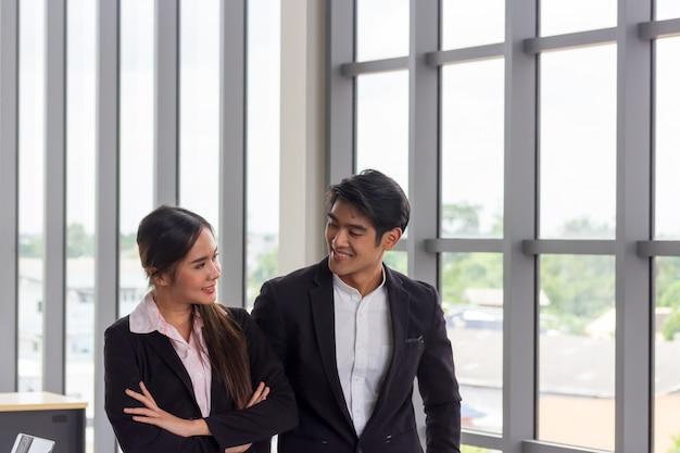 Uomini e donne asiatici di affari che stanno nell'ufficio. il concetto di lavoro di squadra