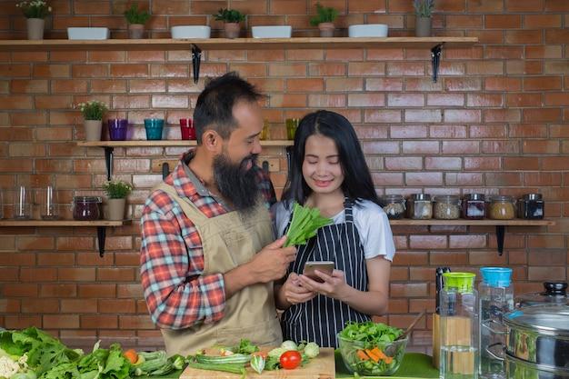 Uomini e donne che si prendono in giro l'un l'altro mentre cucinano in cucina con un muro di mattoni rossi.