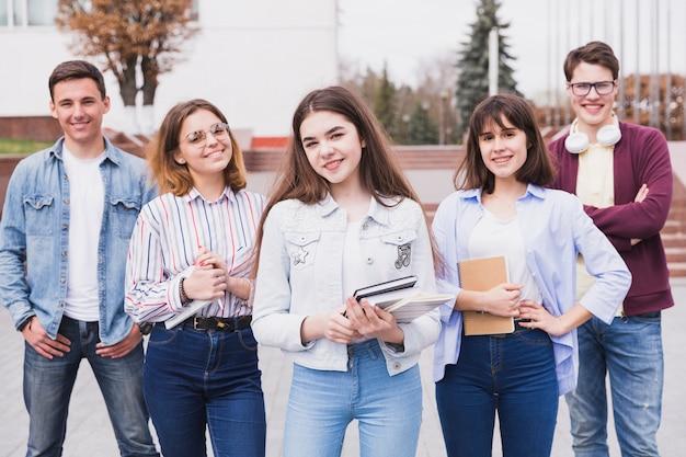 Uomini e donne in piedi con i libri che guarda l'obbiettivo