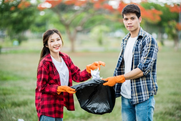 Uomini e donne si aiutano a vicenda per raccogliere i rifiuti.