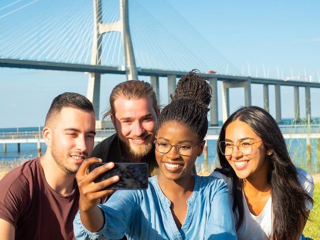 Uomini e donne sorridenti che prendono selfie all'aperto
