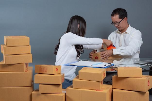 Uomini e donne stanno aiutando a mettere in valigia le scatole.