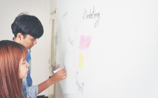 Uomini e donne stanno scrivendo un piano su una lavagna bianca.