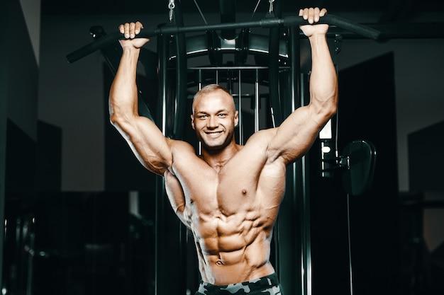 Uomini fitness facendo esercizi di pull-up in palestra