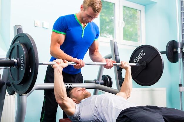 Uomini in palestra sportiva con bilanciere per il fitness