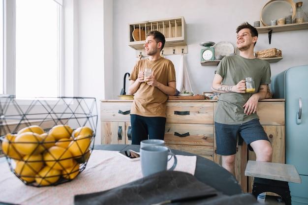 Uomini in possesso di un barattolo di succo guardando attraverso la finestra