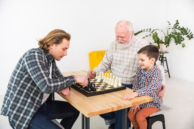 Uomini multigenerazionali che giocano a scacchi