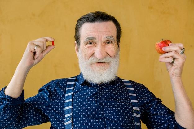 Uomini senior barbuti sorridenti alla moda che tengono pillola rossa in una mano e mela rossa in altra mano, posanti alla macchina fotografica su fondo giallo isolato