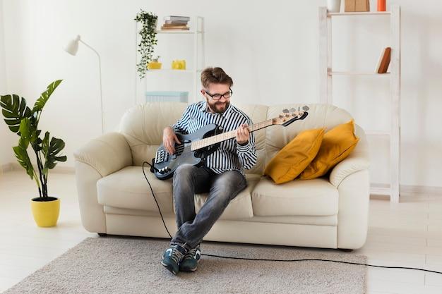 Uomo a casa a suonare la chitarra elettrica