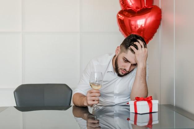 Uomo a casa bevendo vino con palloncini a forma di cuore e presenti a casa
