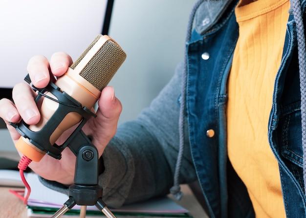 Uomo a casa che parla sul telelavoro del microfono