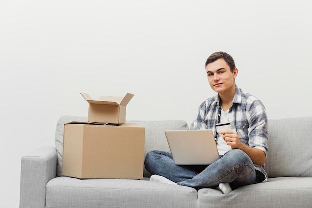 Uomo a casa con scatole da imballaggio